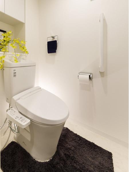 白いトイレ空間の中に、花と小物で華やいだスペースを