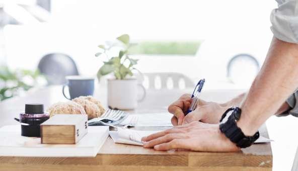 住宅ローン必要書類を作成する男性のイメージ写真